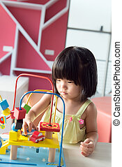 Child playing toy - Little Asian girl playing with toy...