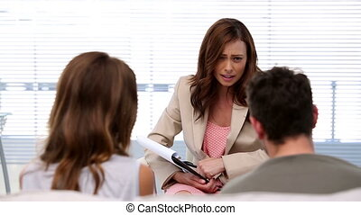Therapist talking to couple on her office