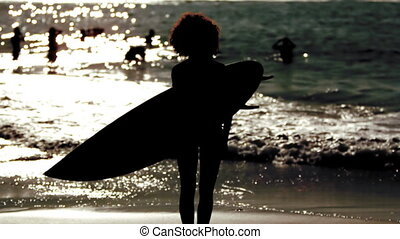 Silhouette of a woman holding surfboard on the beach in slow...