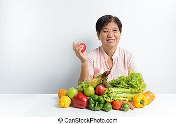 Healthy eating - Elderly woman with pile of vegetables and...