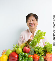 Vegetables and fruits - Elderly woman with pile of...