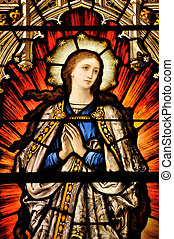 Stained Glass window of St Mary in contemplative prayer