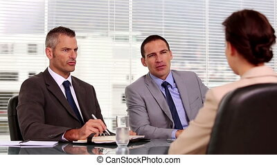 Businessmen talking to an applicant