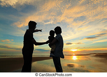 family watching the sunrise on the beach