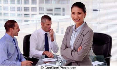 Smiling businesswoman posing while colleagues are working...