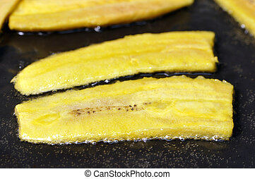 Fried plantains - Closeup of sliced plantain bananas frying...
