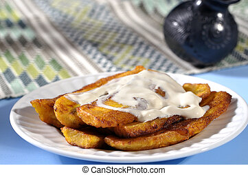 Fried bananas - Stack of fried plantain bananas and cream on...