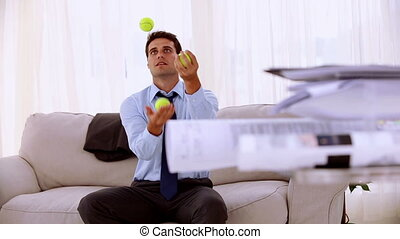 Happy businessman juggling with tennis ball sat on a couch