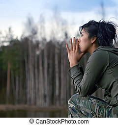 Contemplation - East girl in a camouflage on coast of lake