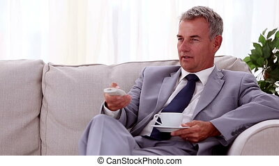 Smiling businessman drinking a cup of tea and holding remote
