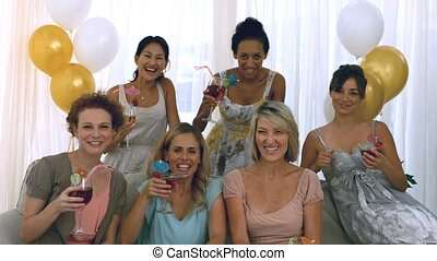 Women toasting with cocktails at a party