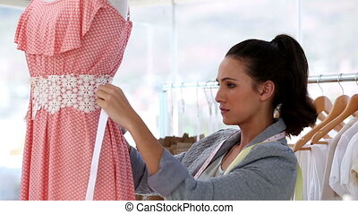 Attractive fashion designer working on a dress in her studio