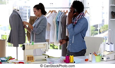 Fashion designer on the phone while discussing with a...