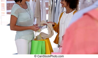 Woman with shopping bags talking with a friend while holding...