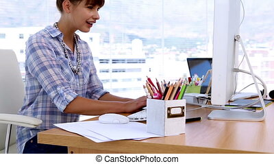 Pretty designer working on computer in his office