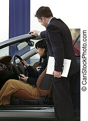 Woman buying car - Young woman buying a car in a showroom...