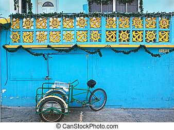 Working Mans Cart - A tricycle waits at a blue wall under a...