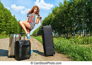 many suitcases - Attractive young woman hitchhiking along a...