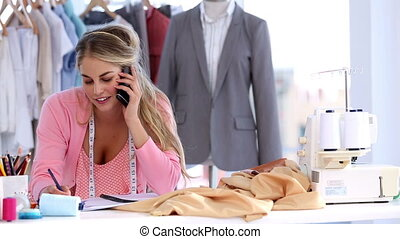 Fashion designer on the phone in a studio
