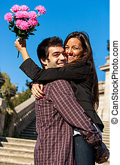 Girl embracing boyfriend with flowers in hand.