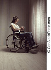 Sad woman sitting on wheelchair - Young woman disabled with...