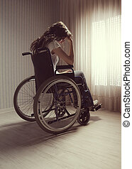 Crying woman sitting in wheelchair by window
