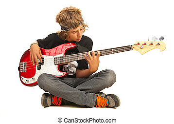 Teen boy playing bass guitar - Teen boy sitting on floor...