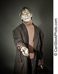 Young actor showing beggar. Old coat and dirty face.