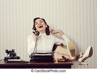 Gossip at phone - Cheerful woman talking on phone at desk