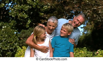 Cheerful multi-generation family embracing in a park in slow...