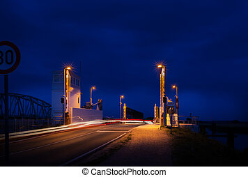 lift bridge - road leading over modern lift bridge at night