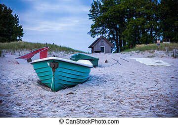 green boat at beach - turquois rowing boat at the beach