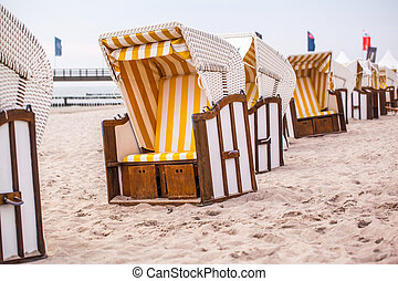 white beach chairs with yello stripes standing on the beach
