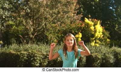 Cute little girl jumping in her garden in slow motion