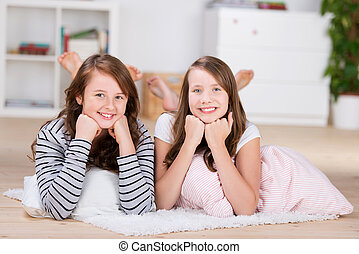 Two pretty young teenage girls laying on the floor - Two...