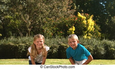 Siblings jumping at the same time in their garden in slow...