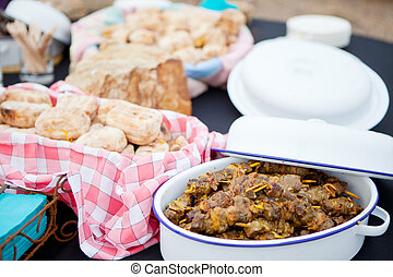 Fresh roasted bread and mutton kebabs in dishes on a table