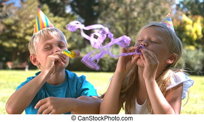 Brother playing with party horn next to his sister while she...