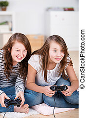 Two young girls happily playing video games in a console...
