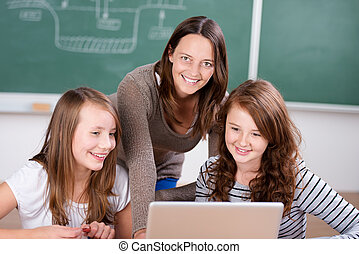 Female teacher teaching her two students with laptop inside...