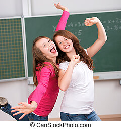 Two happy students - Portrait of two happy students raising...
