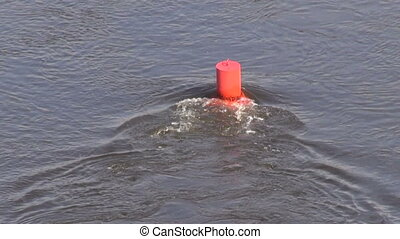 red buoy on river water - floating red buoy on river water
