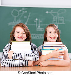 Schoolgirls embracing each a pile of books - Smiling and...