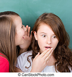 Gossiping girls - Two children sharing a secret in front of...