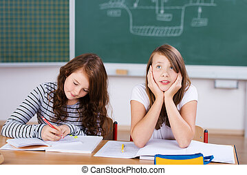 Female students - Two female students in classroom studying...