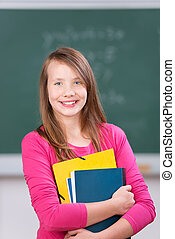 Schoolgirl smiling and holding her notebooks
