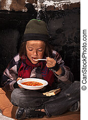 Poor beggar child eating charity food on the street sitting...