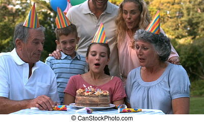Happy family blowing the candles of birthday cake in slow...