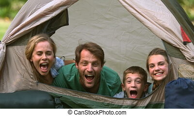 Happy family having fun together in a tent in slow motion