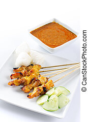 Chicken satay, skewered and grilled meat, served with peanut...